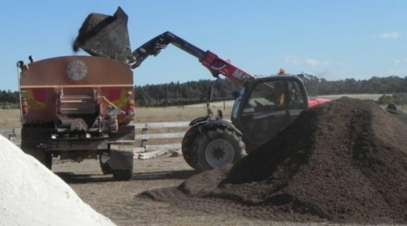tractor piles manure and lime into waiting truck