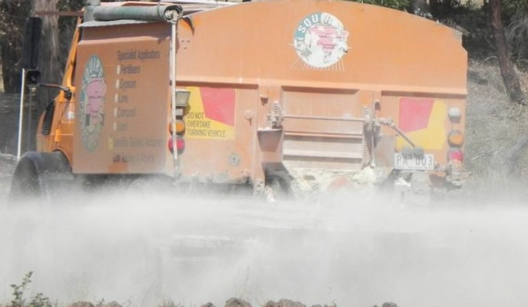 Truck spreads lime on paddock